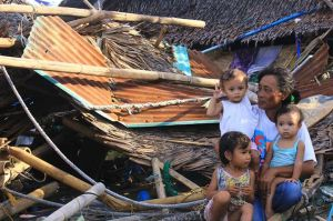 Nanay Emma Pedrano, GABRIELA-Culasi Chapter Chairperson, with her children in front of the rubble of what used to be her house in Roxas City. Capiz Province is one of the most devastated area after the Typhoon Yolanda (Haiyan). Despite government pronouncements, help has yet to reach many communities six days after the devastation. (photos by Jet Canas)